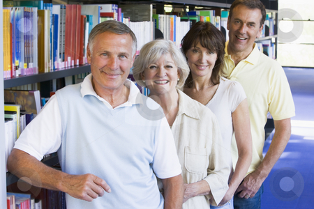 Adult students standing in a library stock photo,  by Monkey Business Images