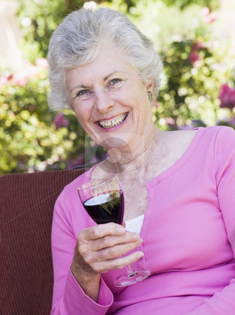 Senior woman enjoying glass of wine stock photo, Senior woman enjoying glass of red wine by Monkey Business Images