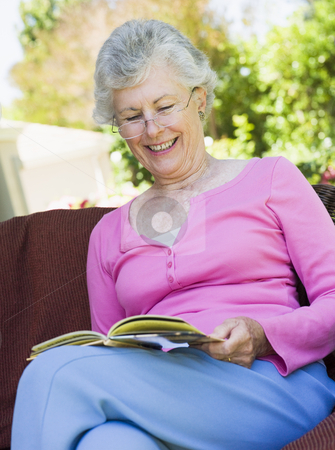 Senior woman reading book outside stock photo, Senior woman sitting on garden seat reading book by Monkey Business Images
