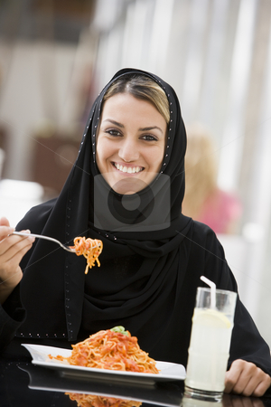 A Middle Eastern woman enjoying a meal in a restaurant stock photo,  by Monkey Business Images