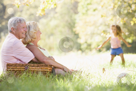 Grandparents at a picnic with young girl in background dancing stock photo,  by Monkey Business Images