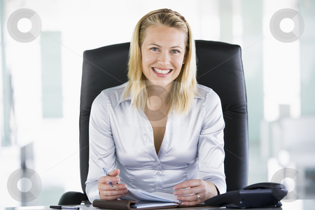Businesswoman in office with personal organizer smiling stock photo,  by Monkey Business Images