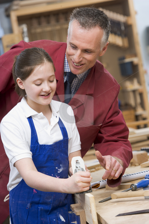 Schoolgirl and teacher in woodwork class stock photo,  by Monkey Business Images