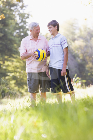 Grandfather and grandson at a park holding a ball and smiling stock photo,  by Monkey Business Images