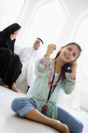 A Middle Eastern girl listening to a mp3 player stock photo,  by Monkey Business Images