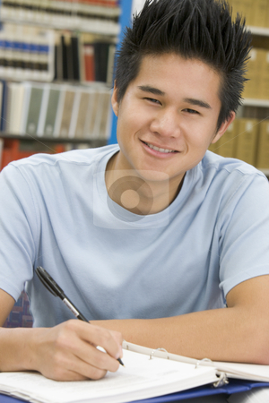 University student working in library stock photo, Male university student writing report in library by Monkey Business Images