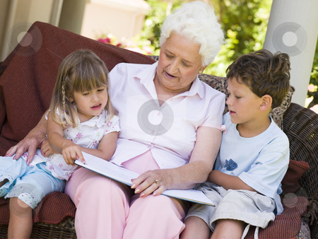 Grandmother reading to grandchildren stock photo,  by Monkey Business Images