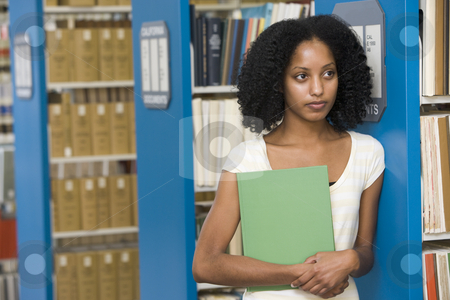 University student working in library stock photo, University student with textbook in library by Monkey Business Images