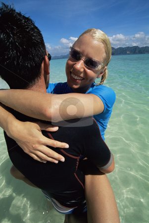 Couple embracing in water at beach stock photo,  by Monkey Business Images