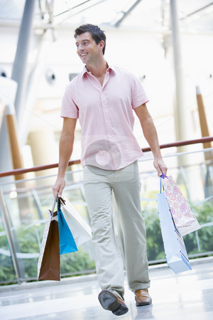 Man shopping in mall  stock photo, Man shopping in mall carrying bags by Monkey Business Images