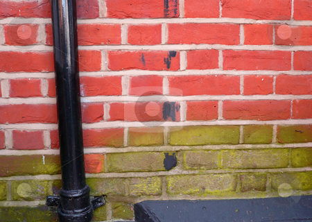 Two tone brick wall stock photo, Old fashioned red brick wall with a black drain pipe by Michael Travers