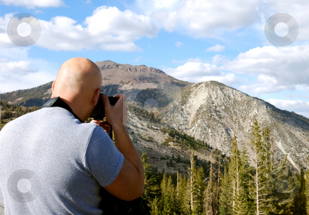 Photographer in Action stock photo, Male photographer shown shooting a picture of a mountain by Denis Radovanovic