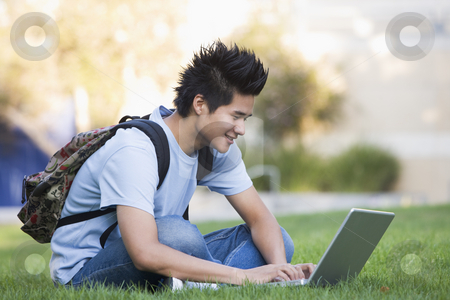 University student using laptop outside stock photo, Male university student sitting on grass with laptop by Monkey Business Images