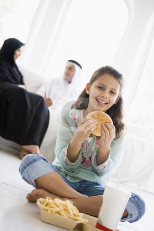 A Middle Eastern girl enjoying a fast food burger meal stock photo,  by Monkey Business Images