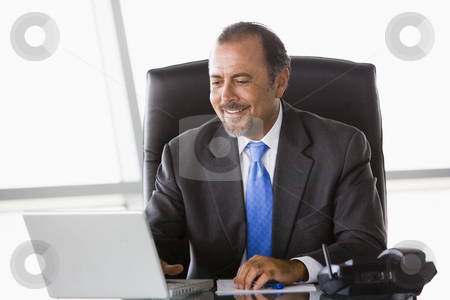 Businessman working at desk stock photo, Businessman working at laptop in office by Monkey Business Images
