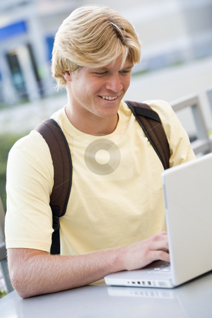 Male student using laptop outside stock photo, Male university student using laptop computer outside by Monkey Business Images