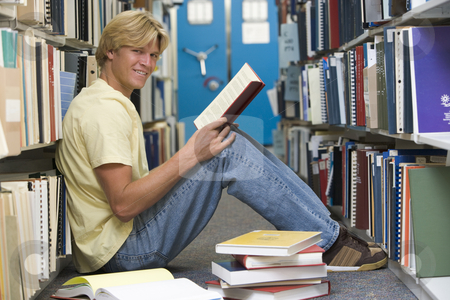 University student working in library stock photo, Male university student sitting on floor surrounded by books by Monkey Business Images