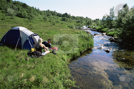 Couple camping next to stream stock photo,  by Monkey Business Images