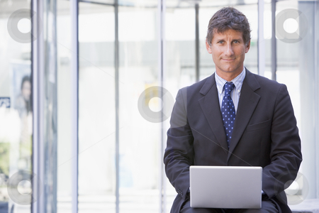 Businessman sitting in office lobby using laptop smiling stock photo,  by Monkey Business Images