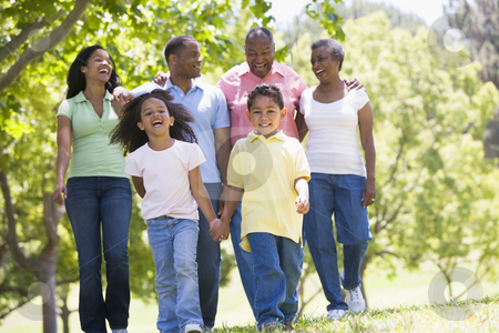 Extended family walking in park holding hands and smiling stock photo,  by Monkey Business Images