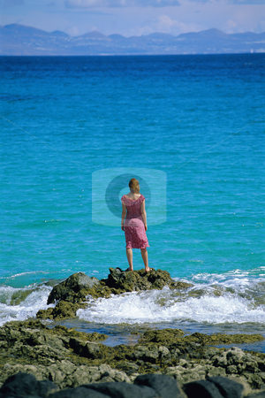 Young woman standing rocks, looking out to sea stock photo,  by Monkey Business Images
