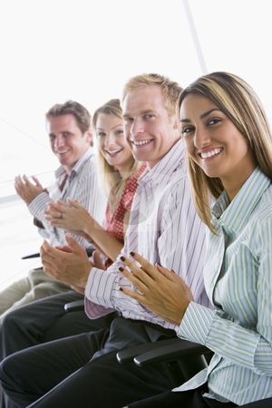 Four businesspeople applauding indoors smiling stock photo,  by Monkey Business Images