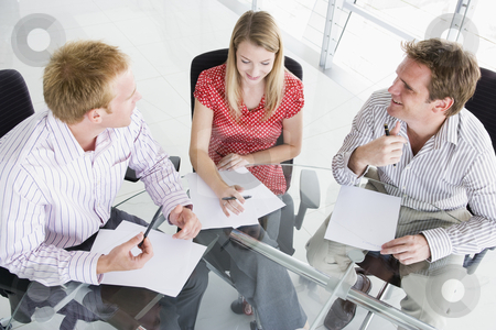 Three businesspeople in a boardroom looking at paperwork stock photo,  by Monkey Business Images