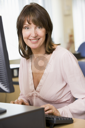 Middle aged woman working on a computer stock photo,  by Monkey Business Images
