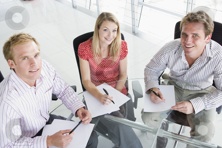 Three businesspeople in a boardroom with paperwork smiling stock photo,  by Monkey Business Images