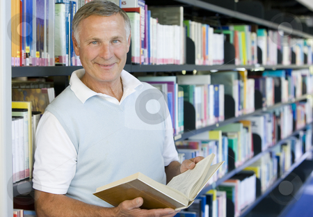 Senior man reading in a library stock photo,  by Monkey Business Images