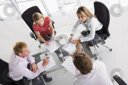 Four businesspeople in a boardroom with paperwork stock photo,  by Monkey Business Images