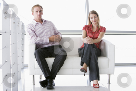 Two businesspeople sitting in office lobby smiling stock photo,  by Monkey Business Images