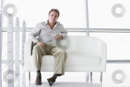 Businessman sitting in office lobby stock photo,  by Monkey Business Images