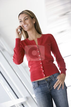 Woman standing in corridor using cellular phone smiling stock photo,  by Monkey Business Images