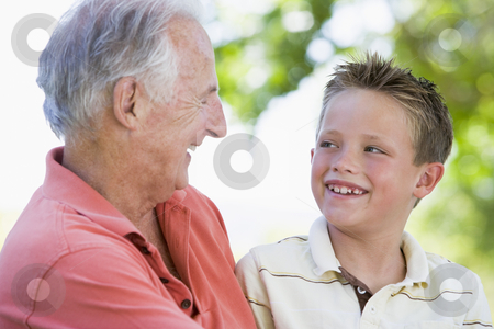 Grandfather and grandson smiling outdoors. stock photo,  by Monkey Business Images