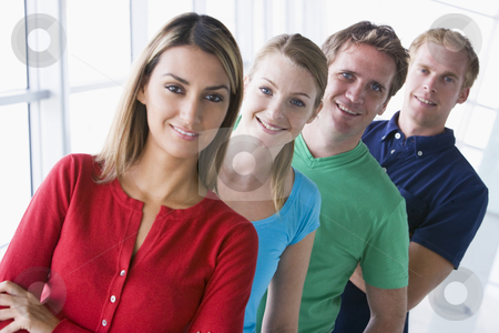 Four people standing in corridor smiling stock photo,  by Monkey Business Images
