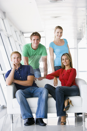 Four people in lobby smiling stock photo,  by Monkey Business Images