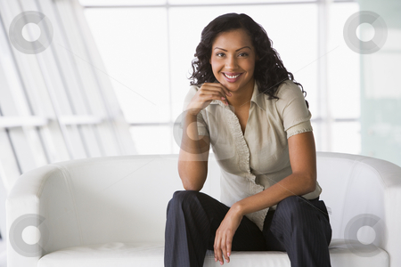 Businesswoman sitting on sofa in lobby stock photo, Businesswoman sitting on sofa in office lobby by Monkey Business Images