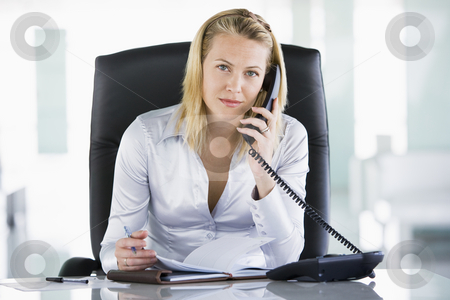 Businesswoman in office with personal organizer open on telephon stock photo,  by Monkey Business Images