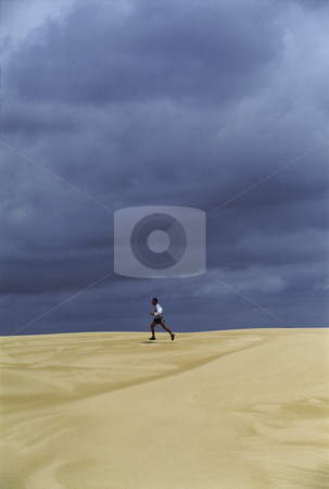 Man running across sand flats stock photo,  by Monkey Business Images