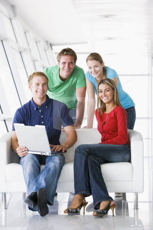 Four people in lobby with laptop smiling stock photo,  by Monkey Business Images