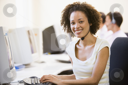 Woman wearing headset in computer room smiling stock photo,  by Monkey Business Images