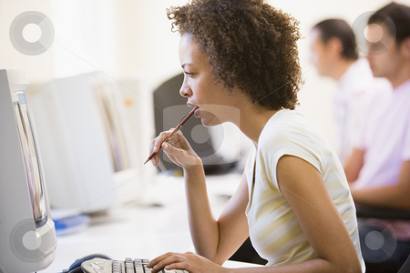 Woman in computer room looking at monitor and thinking stock photo,  by Monkey Business Images
