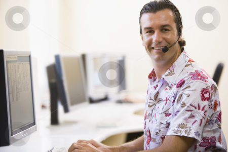 Man wearing headset in computer room smiling stock photo,  by Monkey Business Images