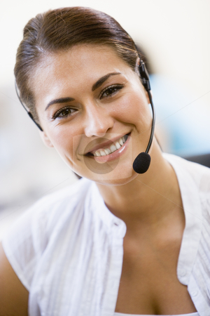 Woman wearing headset indoors smiling stock photo,  by Monkey Business Images