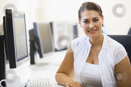 Woman sitting in computer room smiling stock photo,  by Monkey Business Images