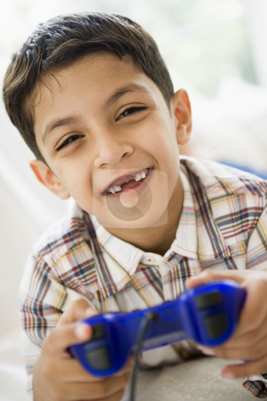 A Middle Eastern boy playing a video game stock photo,  by Monkey Business Images