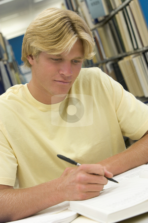 University student working in library stock photo, Male student working on report in library by Monkey Business Images