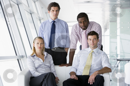 Four businesspeople in office lobby stock photo,  by Monkey Business Images