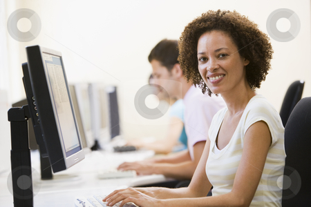 Three people in computer room typing and smiling stock photo,  by Monkey Business Images